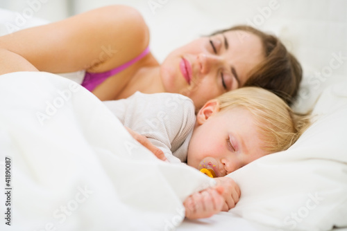 Baby and mother sleeping together in bed