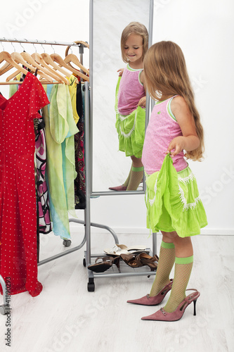 Little girl trying on large shoes