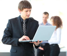 business man using laptop with colleagues in the background