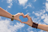 Hands as a hart shape on a cloudy sky - love concept