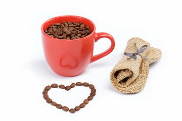 Heart made ​​from coffee beans around a cup of coffee on a w