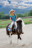 Horseback  riding - little cowgirl is riding a pony poster
