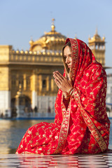 Woman in a red sari praying, Golden Temple in Amritsar, India