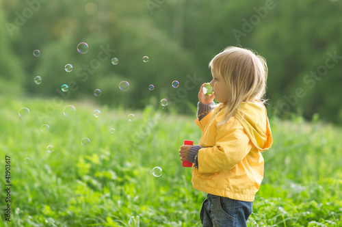 Adorable baby blow soap bubbles in park