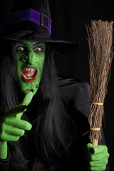 Witch and her broom stick, black background.