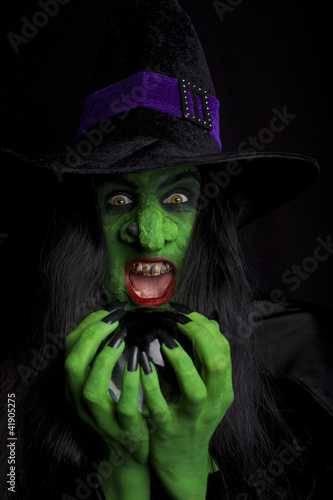 Witch holding her crystal ball, dark background.