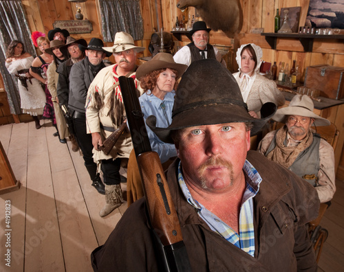Serious Cowboy with Rifle in Saloon