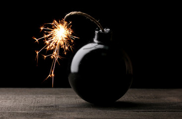 Cartoon style bomb on wooden table on black background