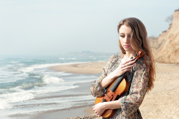 Portrait of beautiful delicate girl with violin on the seashore