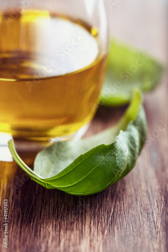 Basil leaves and olive oil on wooden background