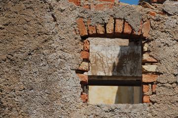 particolare di un vecchio muro con finestrella-rovine