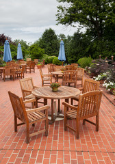 Teak patio tables and chairs on brick deck