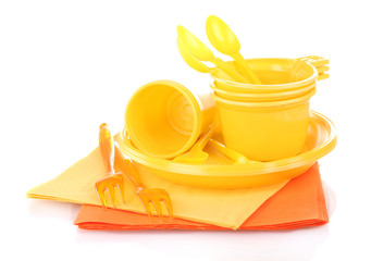 Yellow plastic tableware and napkins isolated on white