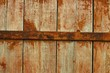 Old wooden door with rusted metal bar