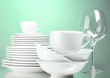 Clean plates, cups and glasses on green background