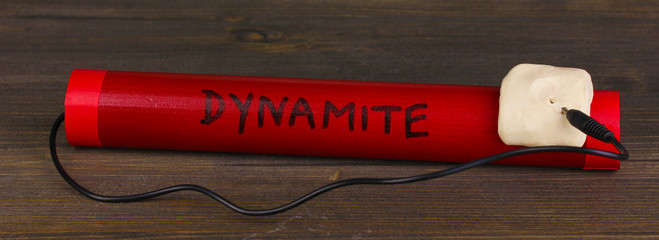 Dynamite on wooden table on grey background