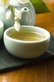 Green tea with jasmine in cup and teapot on wooden table