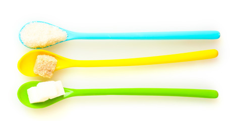 Bright colorful spoons with different types of sugar isolated