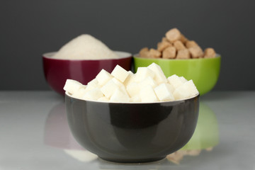 Bowls with different types of sugar on a gray background