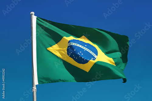 Brazilian flag and pole flutters against Brazil blue skies