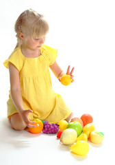The girl in a yellow dress plays with fruit