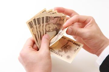 businessman counts Japanese Yen