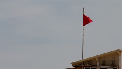 Red flag on the lifeguard booth on the beach