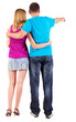 Back view of young couple pointing at wall
