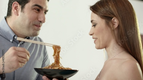 Man and woman having fun and laughing with dish of pasta