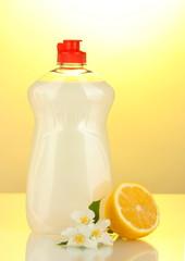 Dishwashing liquid, lemon and flowers on yellow background