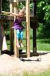 Mädchen springt vom Klettergerüst