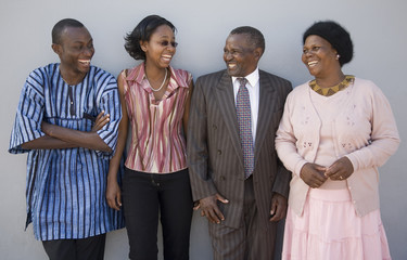4 Happy African people standing together against a wall