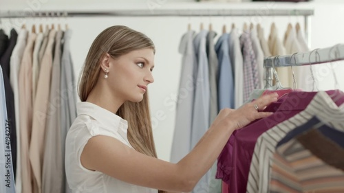 Beautiful girl shopping for clothes in fashion store