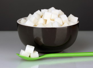Black bowl with white lump sugar with colorful spoon