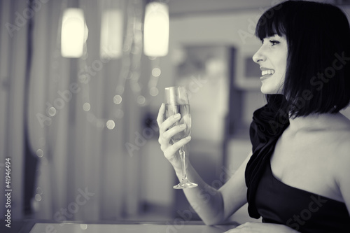 beautiful smiling woman with glass of champagne at restaurant