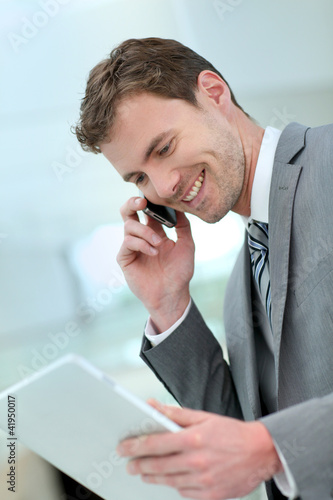 Smiling businessman having a phonecall in building hallway - 41950017