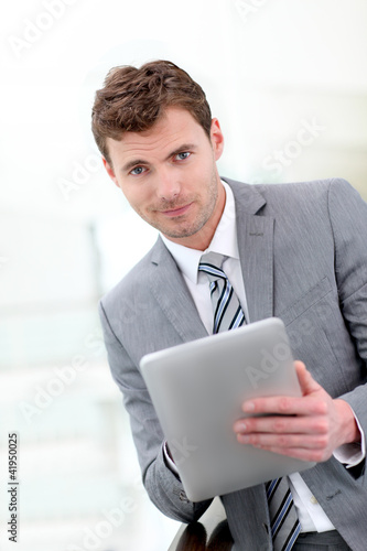 Portrait of businessman using electronic tablet in hall - 41950025