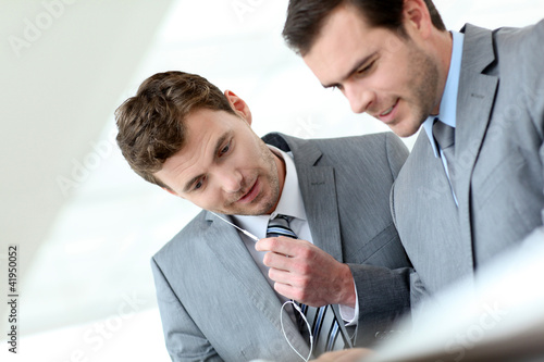 Business partners working in hallway with electronic tablet