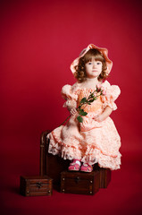 Little girl with rose flower sitting on wooden trunk