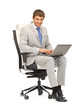 young businessman sitting in chair with laptop