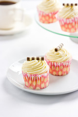 Cream cupcakes with chocolate decoration and tea.
