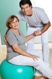 Therapist Helping Senior Woman Sitting On Fitness Ball