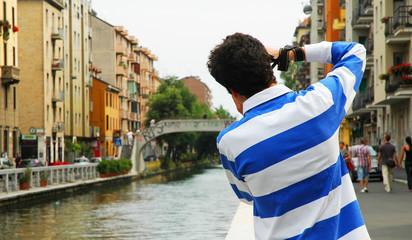 Ragazzo che fotografa i navigli di Milano, Italia