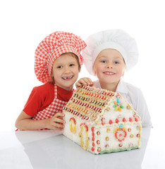 Happy kids cooking gingerbread house