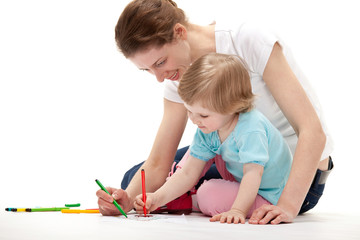 Young mother and her daughter drawing together