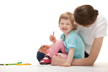 Happy laughing child drawing with her mother