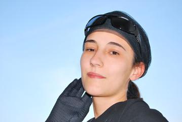 Junge Frau mit schwarzem Handschuh vor blauem Himmel