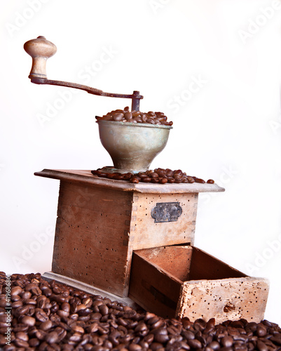 Coffee grinder with coffee beans over white background