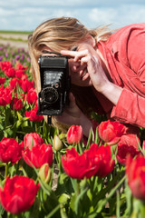 Dutch blond girl with old photo camera in field with tulips