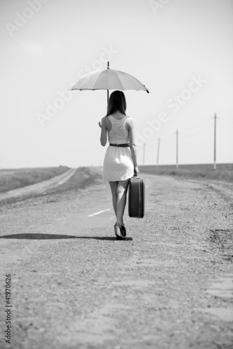 Lonely girl with suitcase and umrella at country road.